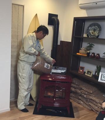 トヨトミ ペレットストーブ 横川社長がエンプレスにペレット燃料を入れる